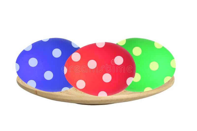 Kolorowi Wielkanocni jajka w drewnianym talerzu odizolowywającym na bielu fotografia stock