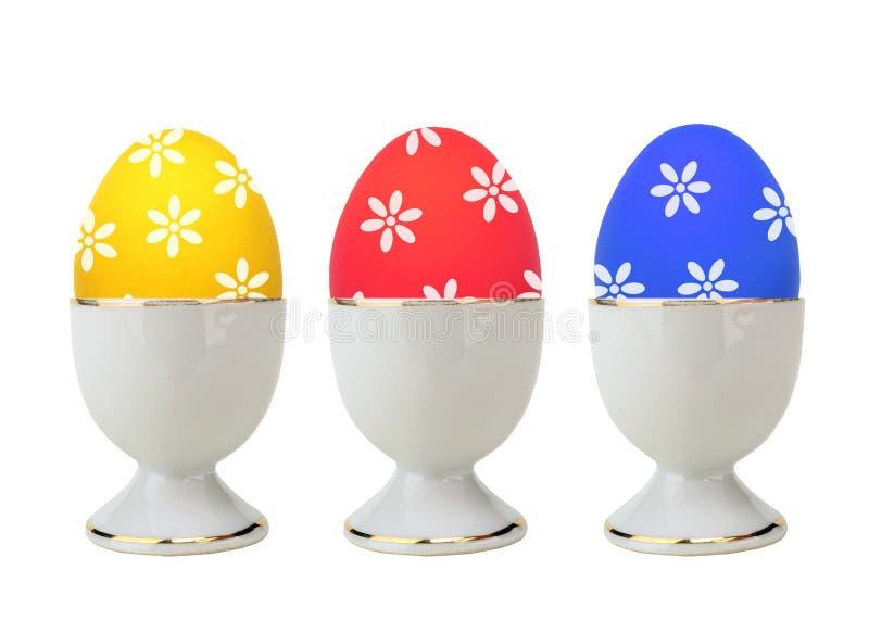 Kolorowi Wielkanocni jajka w stojaku odizolowywającym na bielu obraz stock