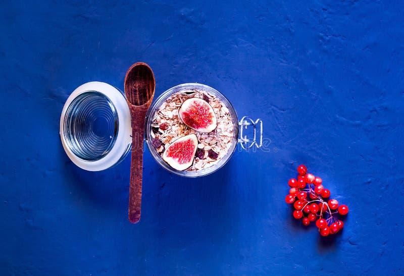 Kolorowy śniadanie, oatmeal z figami w szklanym słoju na błękitnym tle beton Zdrowy łasowania pojęcie, zbliżenie, kopia spacen obrazy royalty free