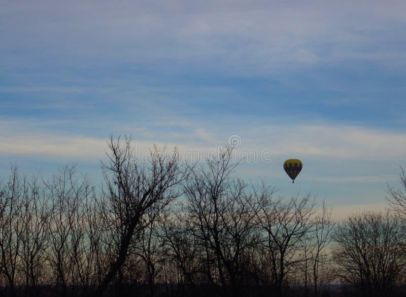 Kolorowy ballon z koszykowym lataniem nad drzewo sylwetki przeciw ranku niebu jako zimy zabawy tło Zima powietrzny sport zdjęcia stock