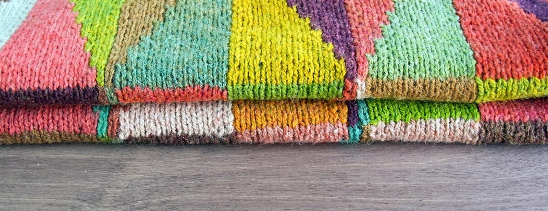 Kolorowy biel, kolor żółty, brąz, menchia, zieleń, błękit, turkus, pomarańcze, claret wełny handmade trykotowy kardigan na drewni zdjęcie stock