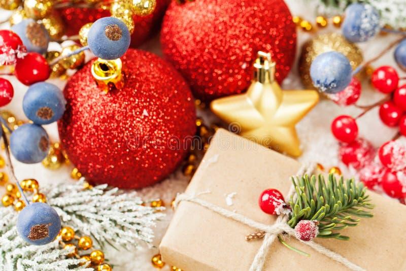 Kolorowy Bożenarodzeniowy skład z prezentem, czerwonymi baubles, uświęconymi jagodami, Xmas gałąź i złotą girlandą na białym śnie zdjęcie royalty free