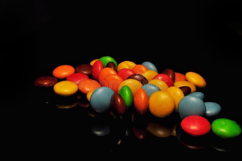 Kolorowy czekoladowy cukierek odizolowywaj?cy na czarnym tle fotografia royalty free