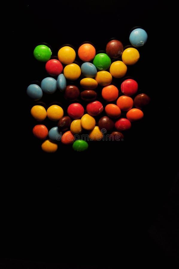 Kolorowy czekoladowy cukierek odizolowywaj?cy na czarnym tle zdjęcia royalty free