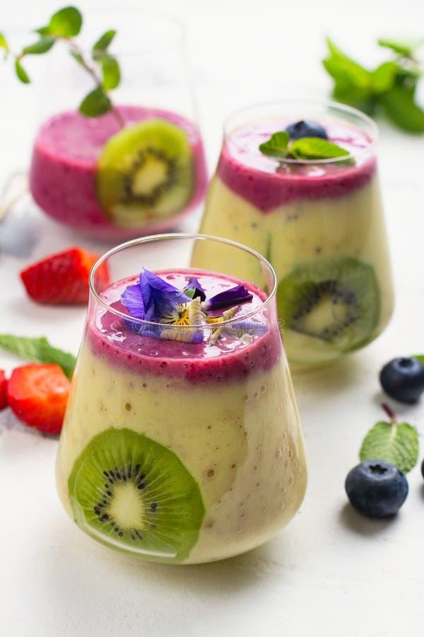 Kolorowy detox ablegrujący smoothie z naturalnymi jadalnymi kwiatami, jagodami i mennicą, zdjęcia royalty free