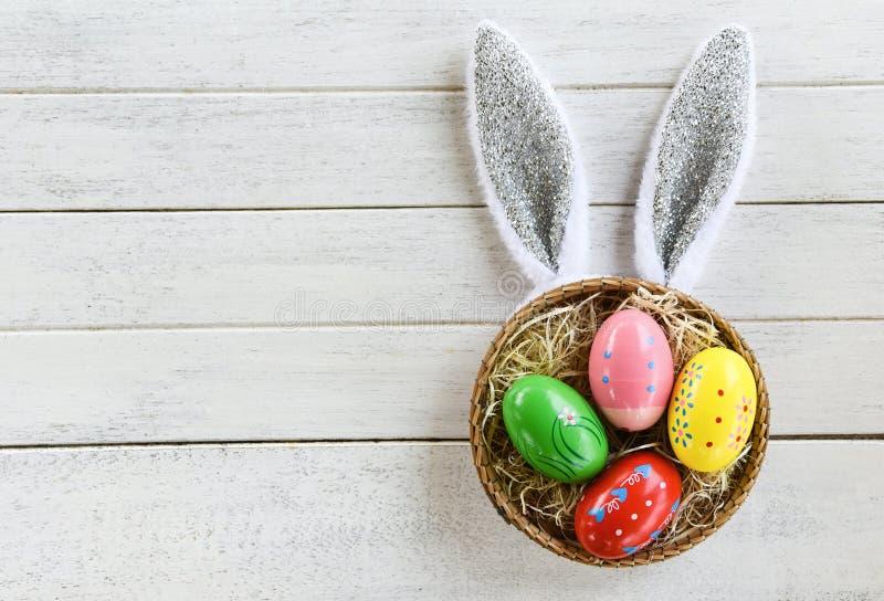 Kolorowy Easter jajek i Easter królika królika uszaty kosz gniazduje dekorację na białego drewnianego tła odgórnym widoku fotografia stock