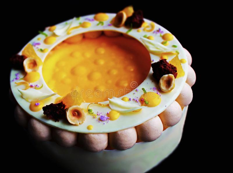 Kolorowy galanteryjny pomarańcze i hazelnut cheesecake odizolowywający na czarnym tle obrazy royalty free
