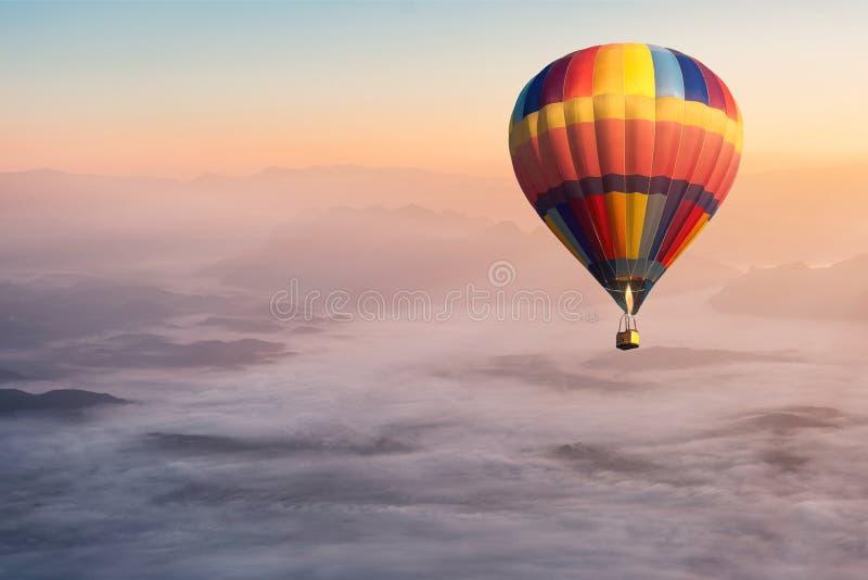 Kolorowy gorące powietrze balonu latanie w powietrzu z mgły i scenerii górami obraz royalty free