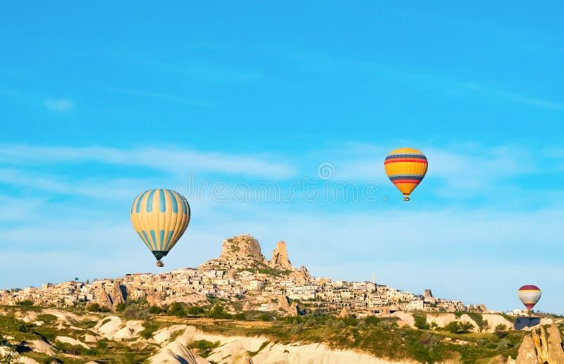 Kolorowy gorące powietrze szybko się zwiększać latanie blisko Uchisar kasztelu przy wschodem słońca, Cappadocia, Turcja fotografia royalty free