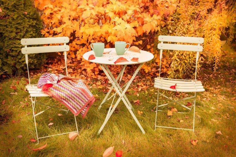 Kolorowy jesień ogródu kącik z gorącą herbatą i koc obrazy royalty free