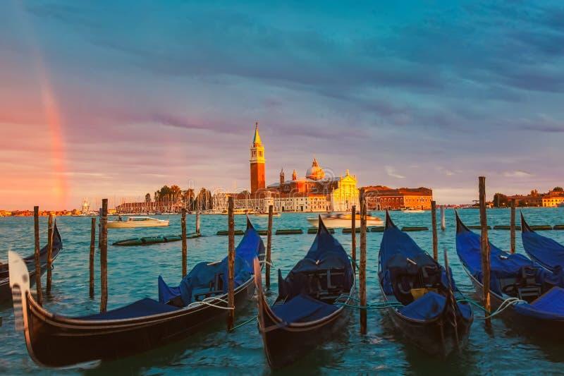 Kolorowy krajobraz z niebem, t?cz? i gondolami zmierzchu, parkowa? blisko piazza San Marco w Wenecja Kościół San Giorgio Maggiore fotografia stock