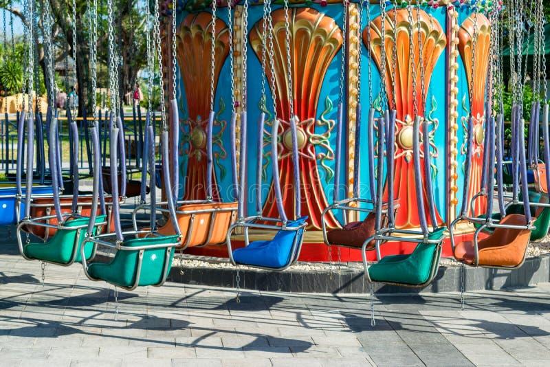 Kolorowy metal huśta się na łańcuchach w parku rozrywkim bez ludzi obraz stock