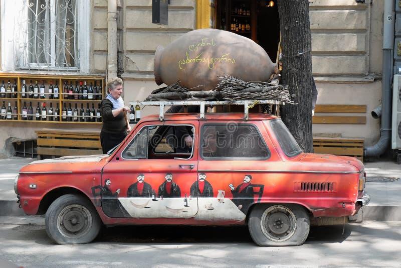 Kolorowy retro Radziecki czerwony samochód z obrazkami i dzbanek na dachu zabawa artistically i przyciągamy uwagę przy wejści zdjęcie stock