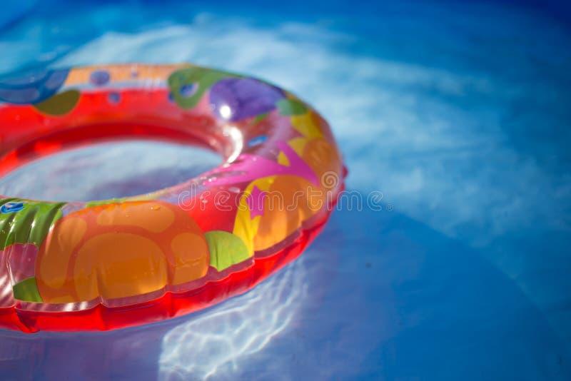 Kolorowy ringowy unosić się w odświeżającym błękitnym basenie obrazy stock