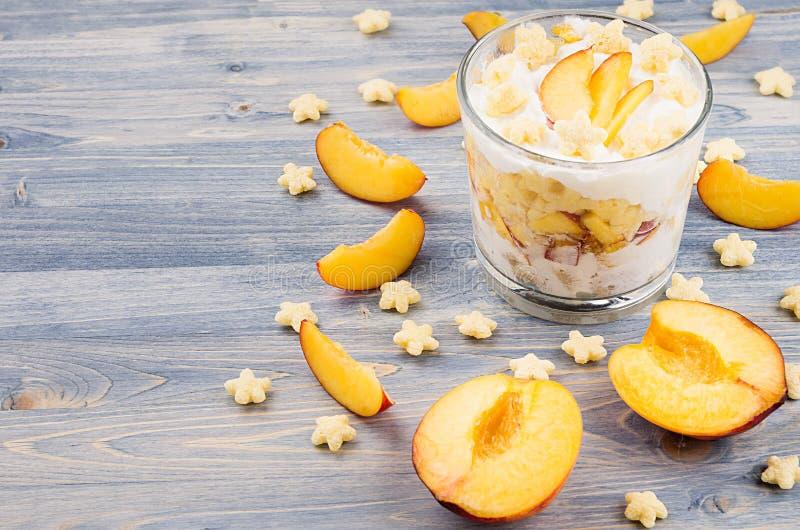 Kolorowy rozochocony śniadanie z jogurtem, gwiazd cornflakes plasterka dojrzała brzoskwinia na błękitnej drewno desce Dekoracyjna fotografia stock