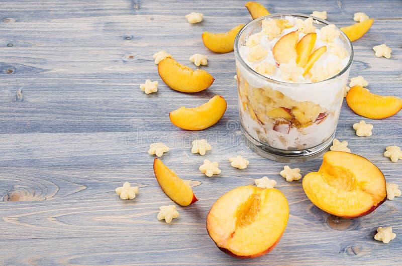 Kolorowy rozochocony śniadanie z jogurtem, gwiazd cornflakes plasterka dojrzała brzoskwinia na błękitnej drewno desce zdjęcie stock