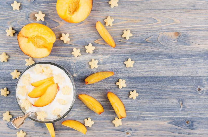 Kolorowy rozochocony smoothie z jogurtem, gwiazda kukurydzanych płatków plasterka dojrzała brzoskwinia na błękitnej drewno desce, zdjęcia royalty free