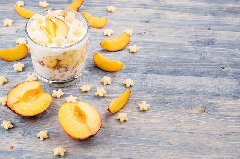 Kolorowy rozochocony smoothie z jogurtem, gwiazda kukurydzanych płatków plasterka dojrzała brzoskwinia na błękitnej drewno desce  fotografia royalty free