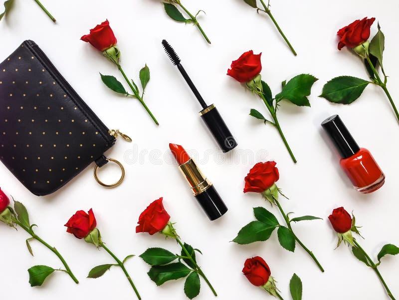 Kolorowy skład z czerwonymi jaskrawymi różami i kobiet akcesoriami Mieszkanie kłaść na bielu stole, odgórny widok fotografia stock