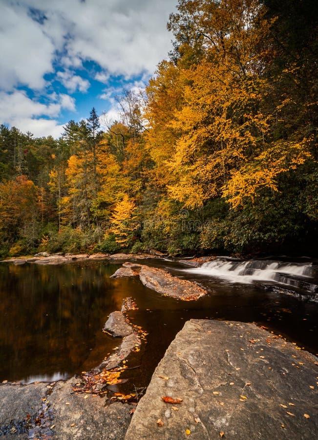 Kolorowy spadku ulistnienia las i rzeka krajobraz z małą siklawą obraz stock