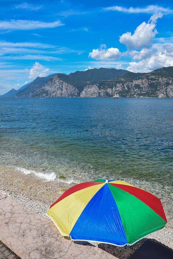 Kolorowy sunshade przy garda jeziornym brzeg, żaglówka na jeziorze i góry za, fotografia stock