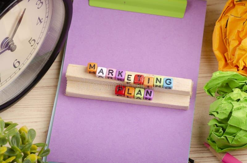 Kolorowy sześcian z słowa MARKETINGOWYM planem na drewnianym biurku obrazy stock