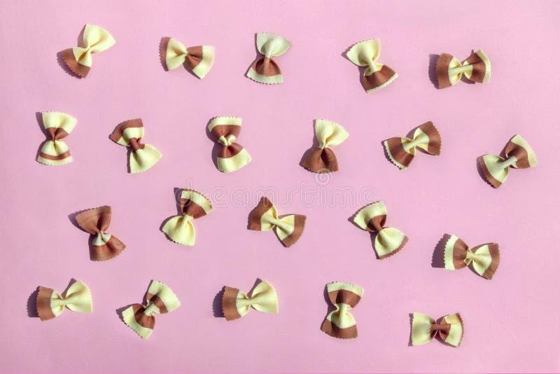 Kolorowy Włoski makaron ono kłania się na różowym tle Suchy makaron dla gotować zdrowego jedzenie, odgórny widok, mieszkanie niea obraz royalty free
