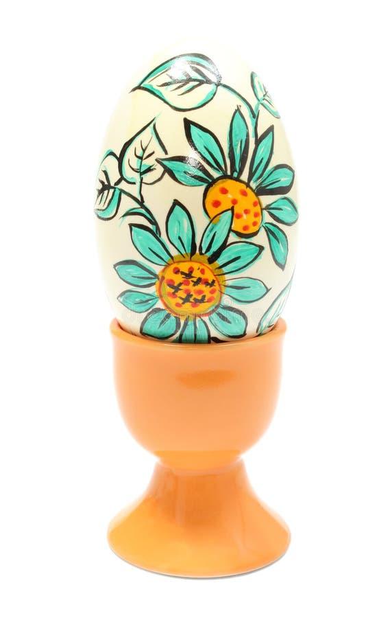 Kolorowy Wielkanocny jajko w pomarańczowej filiżance. Odizolowywający na białym tle fotografia royalty free