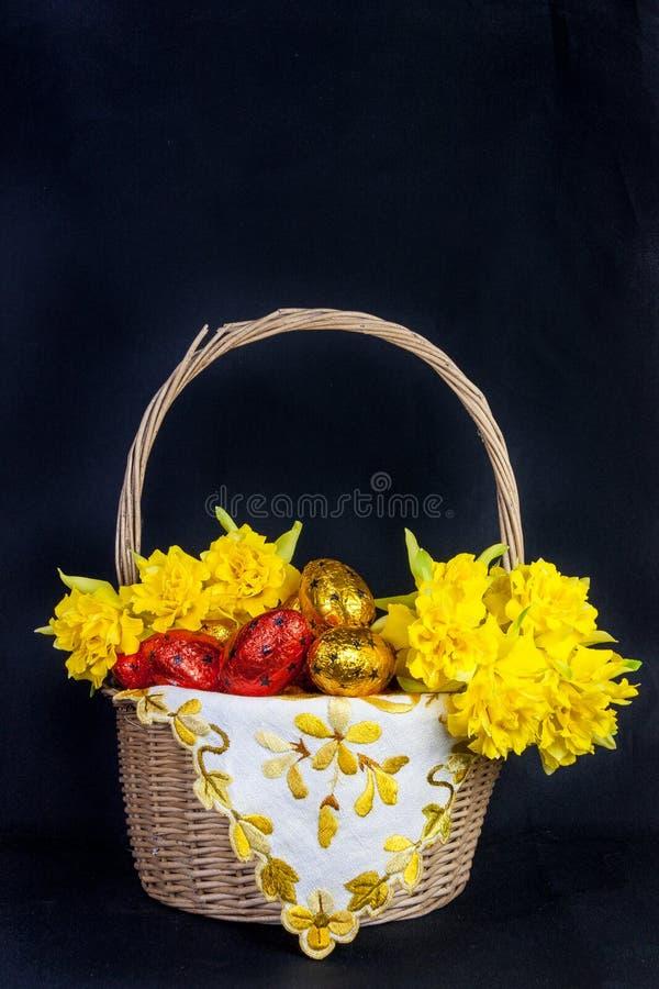 Kolorowy Wielkanocny kosz z Estrowymi jajkami i daffodils fotografia royalty free