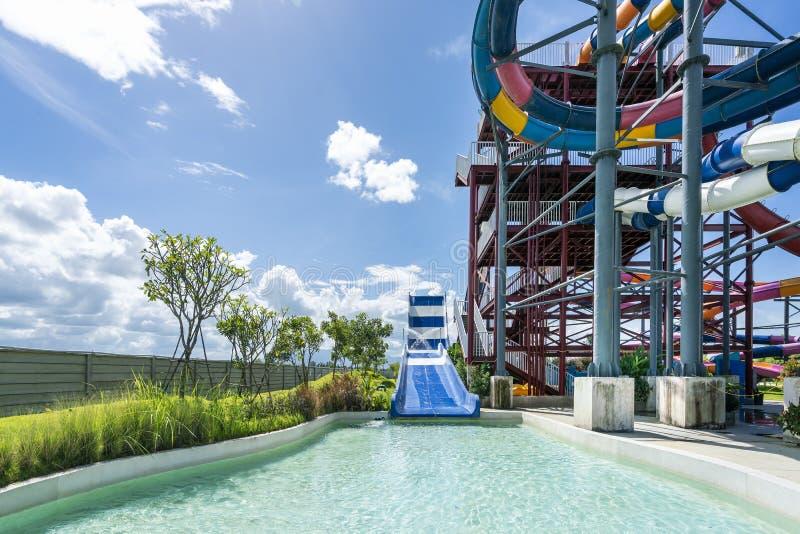 Kolorowy wielki suwak, basen przy rozrywki wody parkiem i aquapark w pięknym dniu chmurnego i niebieskiego nieba zdjęcie stock