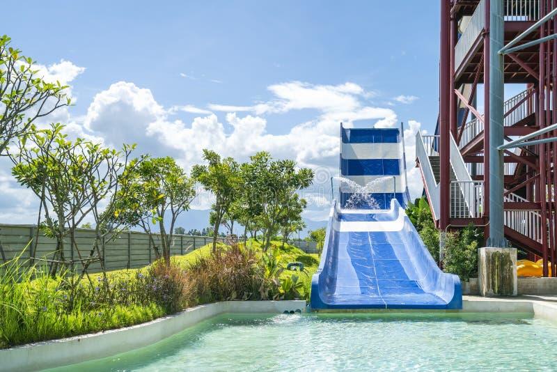 Kolorowy wielki suwak, basen przy rozrywki wody parkiem i aquapark w pięknym dniu chmurnego i niebieskiego nieba obraz royalty free