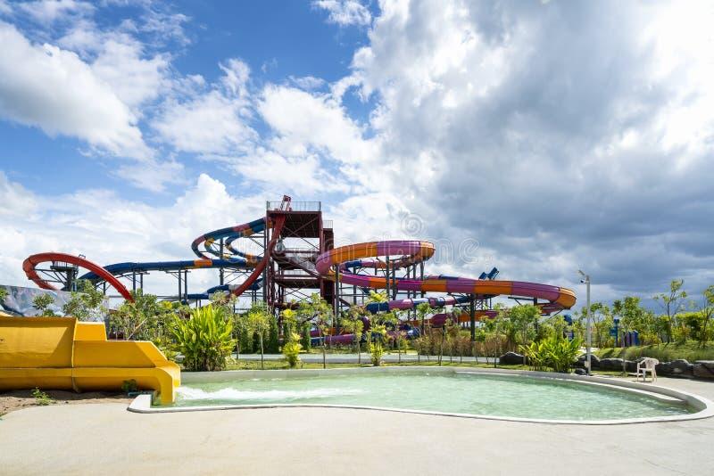 Kolorowy wielki suwak i basen przy rozrywki wody parkiem w dniu chmurnego i niebieskiego nieba zdjęcie stock