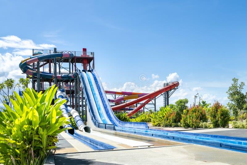 Kolorowy wielki suwak przy rozrywki wody parkiem lub aquapark w pięknym dniu chmurnego i niebieskiego nieba zdjęcie royalty free