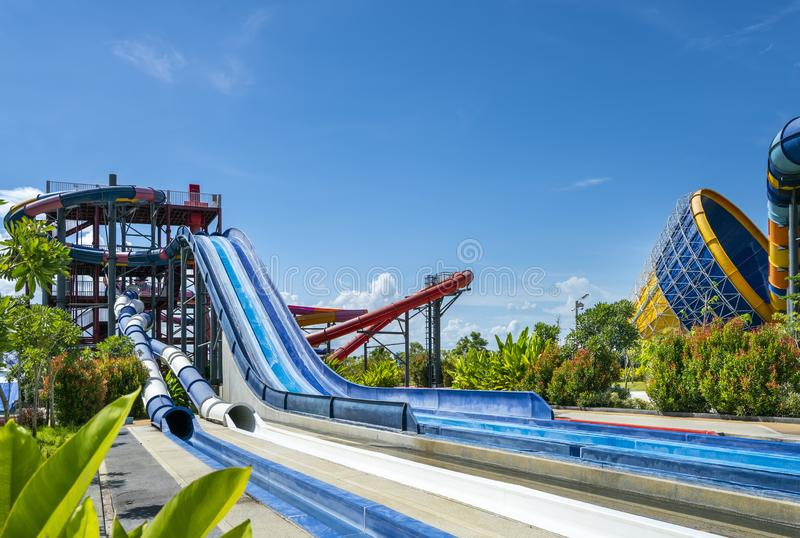 Kolorowy wielki suwak przy rozrywki wody parkiem lub aquapark w pięknym niebieskie niebo dniu zdjęcia royalty free