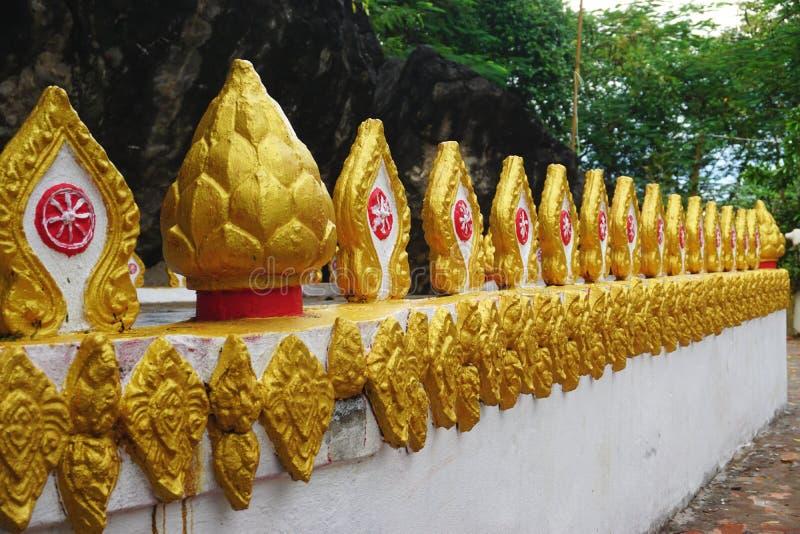 Kolorowy złoto malował dekoracje na ścianie blisko Buddyjskiej świątyni w Luang Prabang, Laos zdjęcia stock