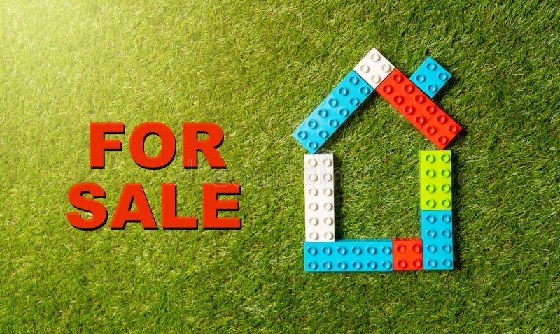 Kolorowy zabawkarski bloku dom Dla sprzedaż teksta Pisać na zielonej trawie w Inwestorskim Majątkowym przemysle i obrazy royalty free