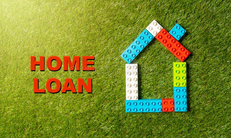 Kolorowy zabawkarski bloku tex, domu kredyt mieszkaniowy pisać na trawie w inwestycji i zdjęcie stock