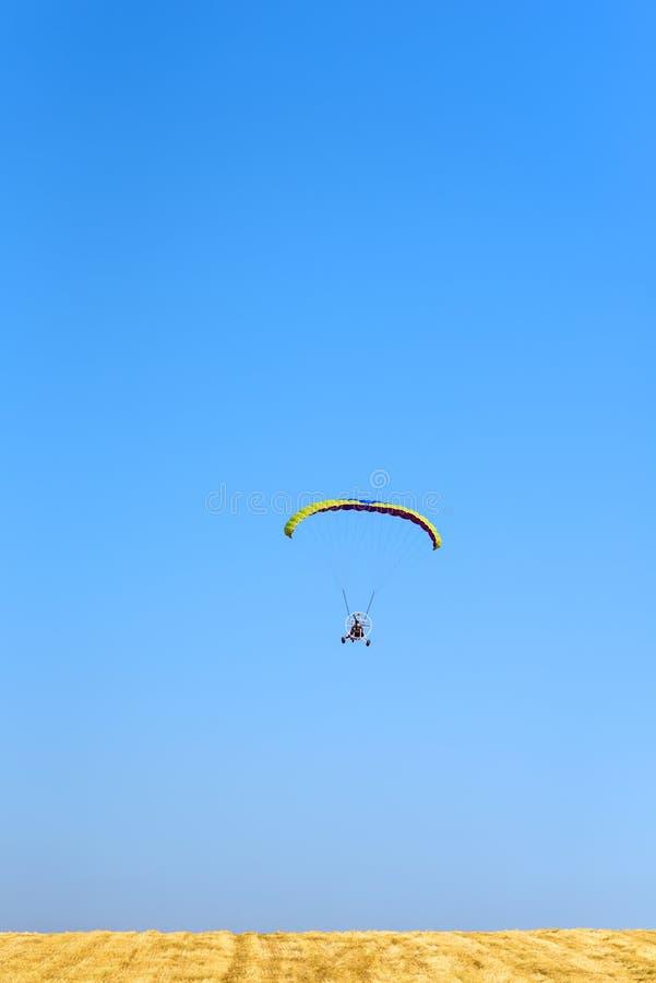 Kolorowy zasilany spadochron przeciw niebieskiemu niebu i koloru żółtego polu obraz stock