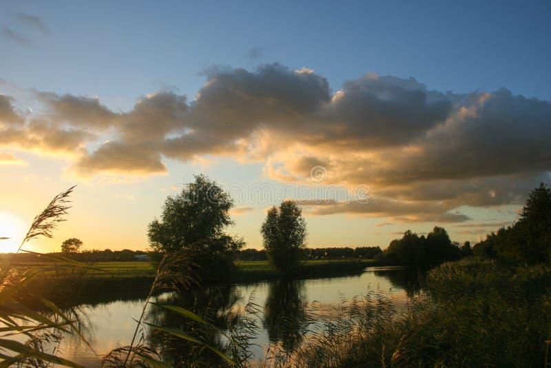 Kolorowy zmierzch z cumulus chmurami nad małym jeziorem blisko Gouda holandie obrazy stock