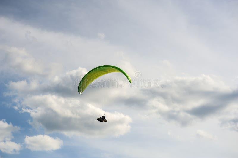 Koloru żółtego i zieleni paraglider lata w niebieskim niebie przeciw tłu chmury obrazy royalty free