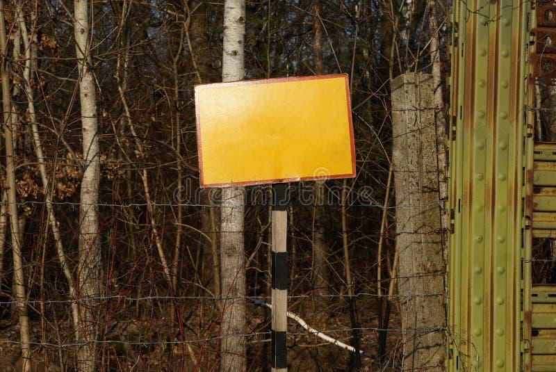 Koloru żółtego talerz na pasiastej kolumnie przy ogrodzeniem żelazo i drut kolczasty zdjęcie stock