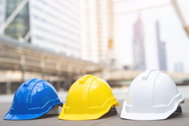 Koloru żółtego, błękitnego i białego ciężki zbawczy odzież hełma kapelusz w projekcie przy budową, robociarz jak inżyniera lub pr obraz stock