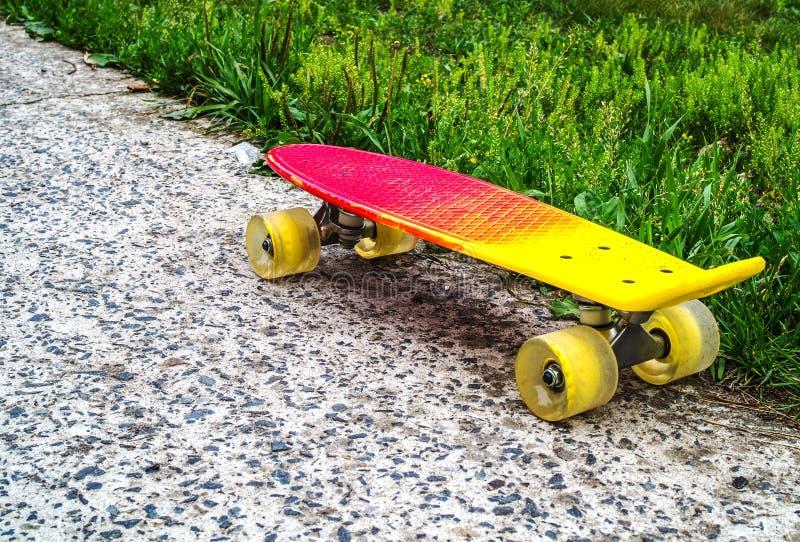 Koloru żółtego centu deska z kolorem żółtym toczy na krawędzi asfaltu i trawy przemiany fotografia royalty free