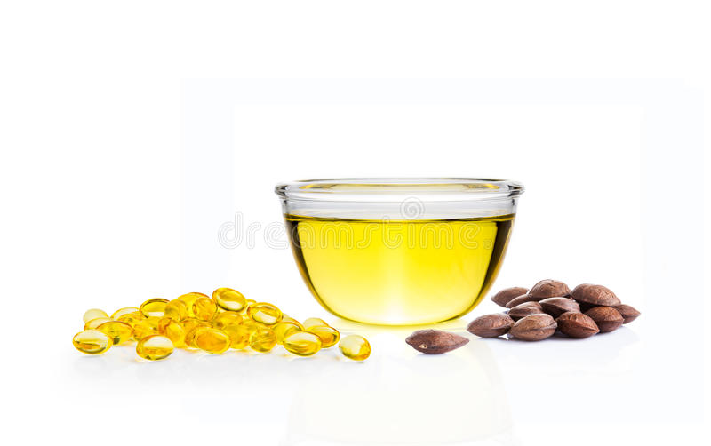 Koloru żółtego olej w szklanym pucharze, gel pigułkach i Sacha Inchi surowych ziarnach o, zdjęcie royalty free