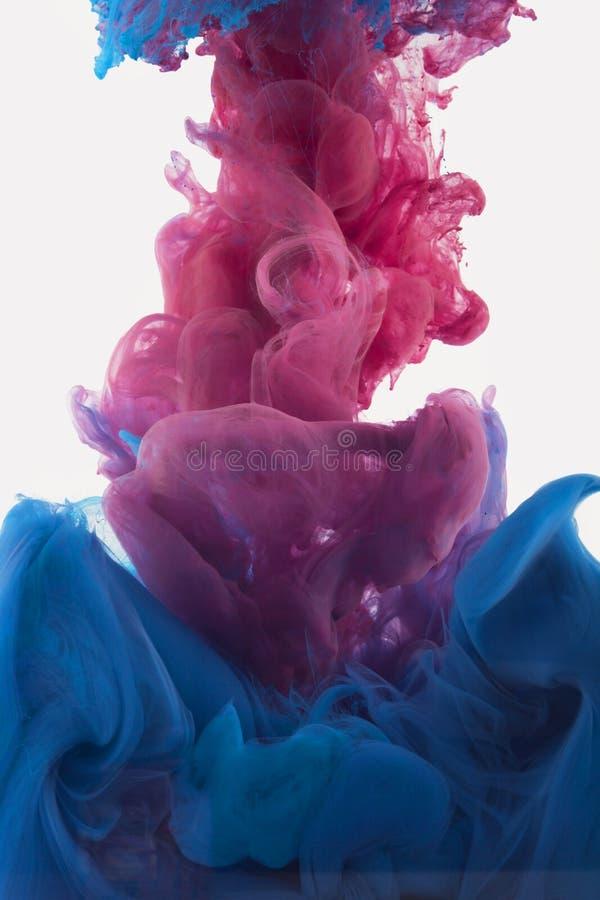 Koloru atramentu kropla w wodzie czerwonawy fiołek, głęboki błękit zdjęcia royalty free