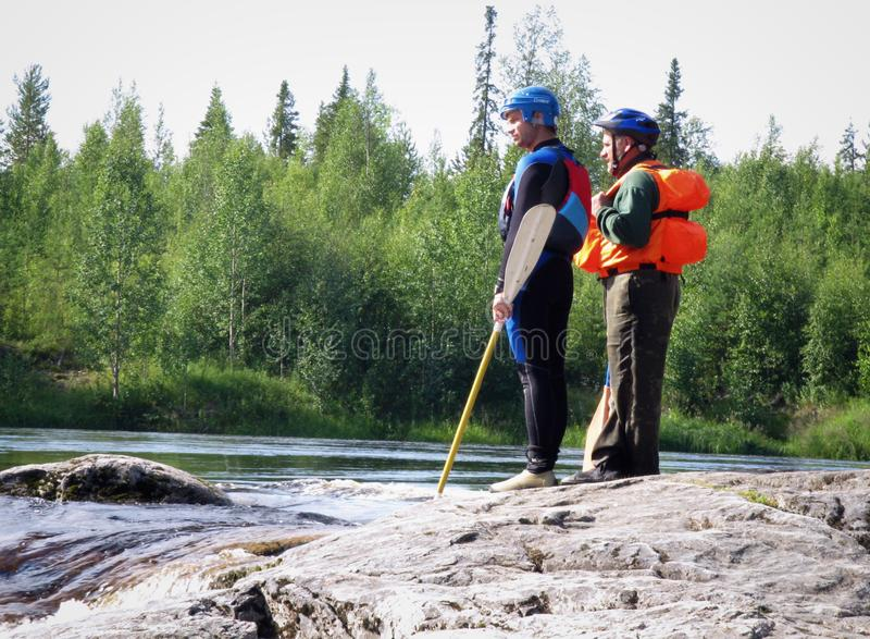 Men. KOLSKYY, RUSSIA - 17 August 2008: Men in the life vest examines threshold mountain river royalty free stock photo