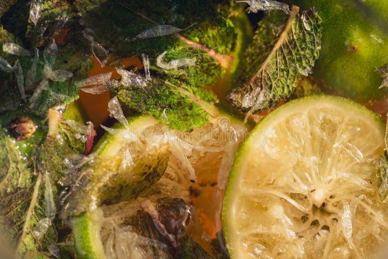 Kolsyrat sodavattenvatten eller fruktsaft med limefrukt och mintkaramellen i en glass tillbringare Makrocloseup arkivfoto