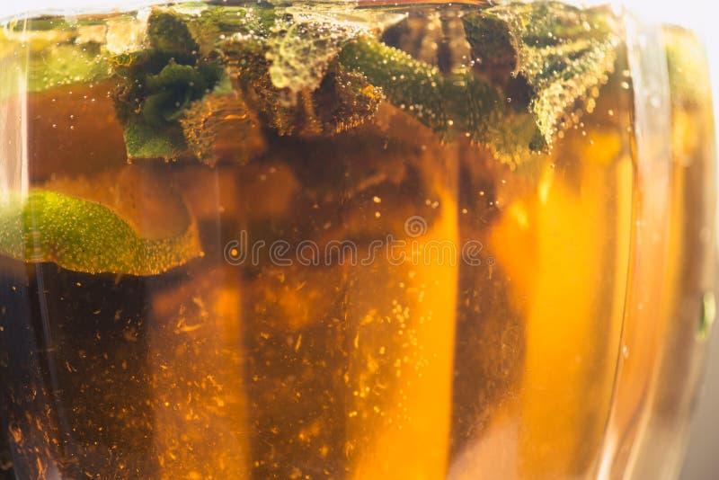 Kolsyrat sodavattenvatten eller fruktsaft med limefrukt och mintkaramellen i en glass tillbringare Makrocloseup royaltyfri foto