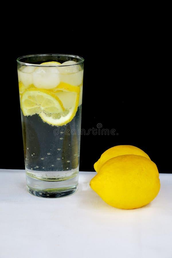 Kolsyrat vatten med citronen i ett genomskinligt exponeringsglas p? en svart bakgrund arkivfoto