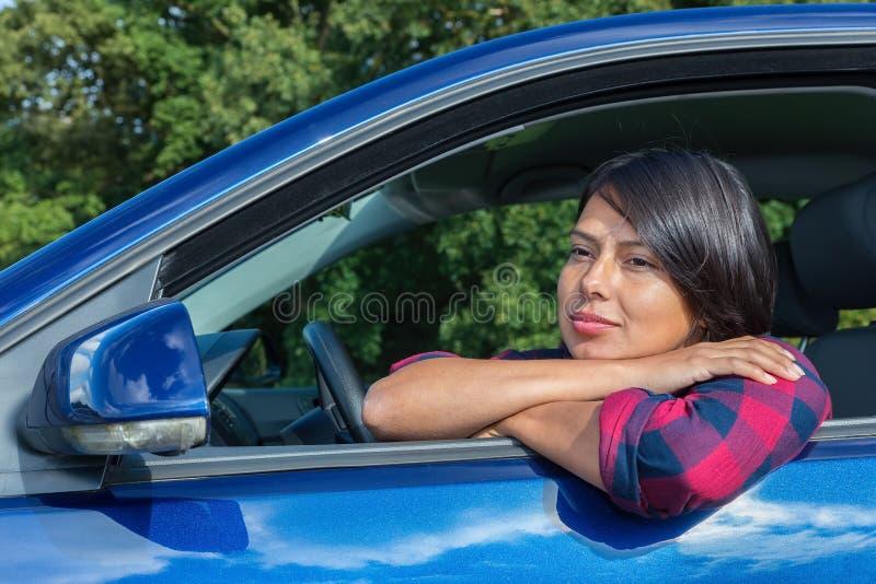 Kolumbijska kobieta cieszy się słońce za samochodowym kołem fotografia royalty free